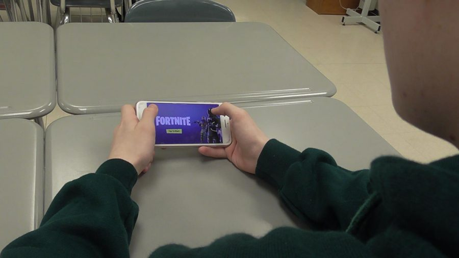 Student sits playing Fortnite during free time in class. Fortnite is the new gaming trend that a majority of people are playing.