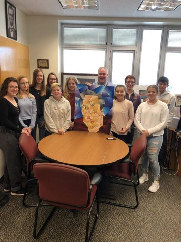 Bill August is with the ten freshmen who surprised him with a cubism painting of himself.  After the idea was suggested to the students, they volunteered their time to paint this piece as a surprise for August.