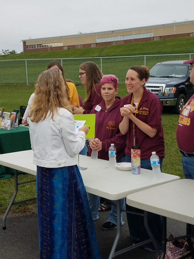 Science teachers Amanda Frankford (right) and Rebecca Herendeen (left) engage with a parent at the Back to School tailgate. The event was used for parents to connect with their child's teachers.